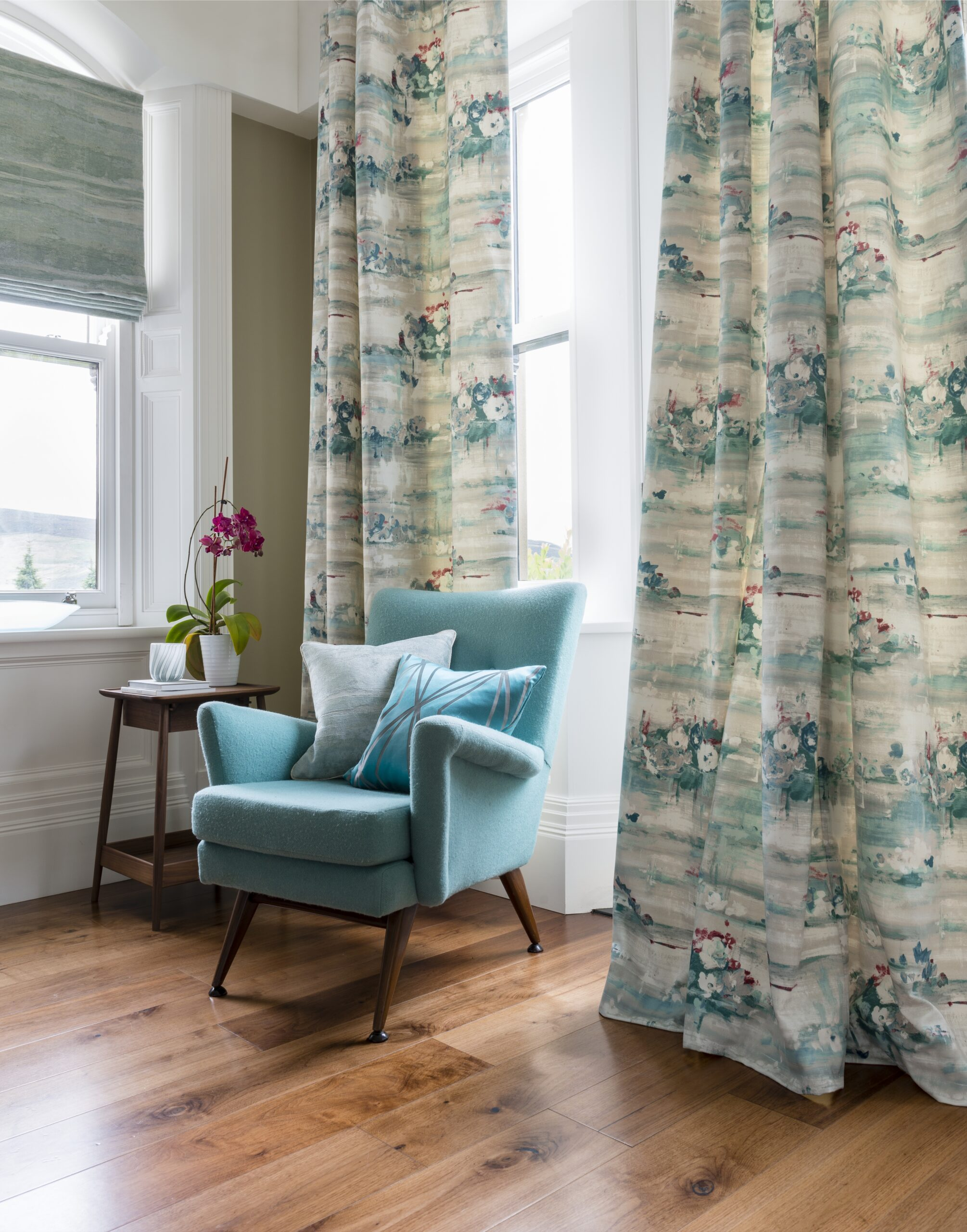 Nice teal chair next to windows covered with beautiful curtains